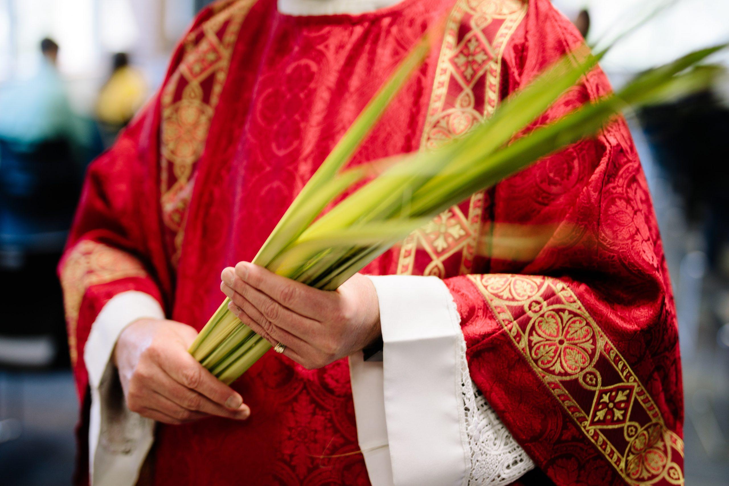 Cura sujetando hojas de palma durante Semana Santa