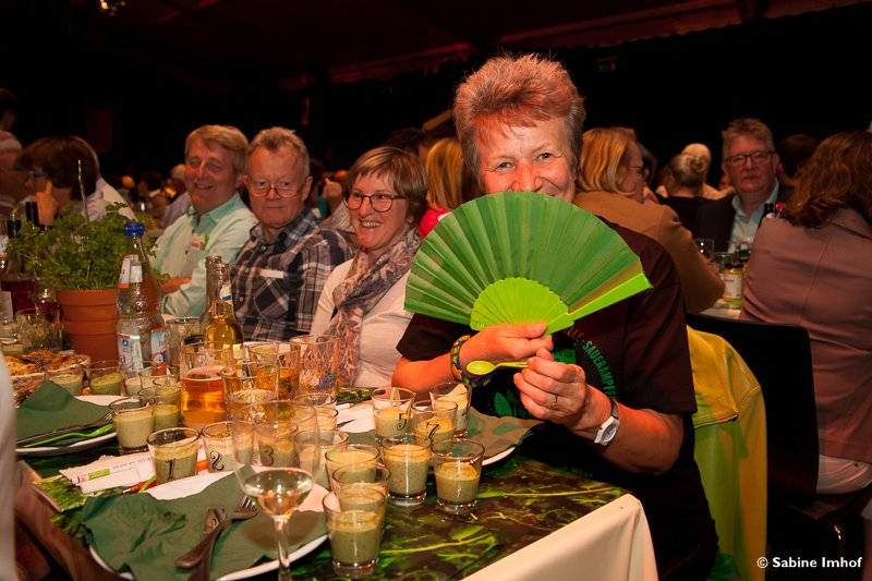 A group of visitors at the Frankfurt Green Sauce Festival, sitting on a table and eating Green Sauce