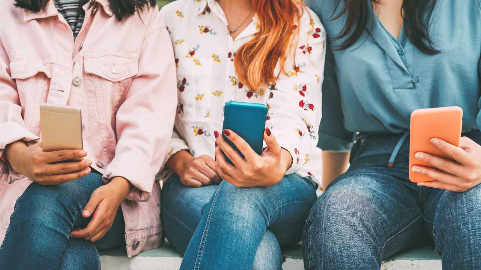 Imagen de adolescentes de la generación Z mirando memes en el móvil